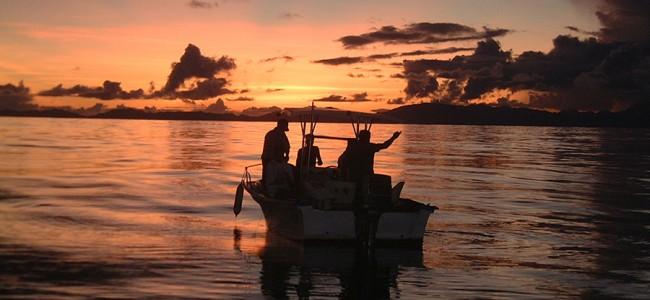 Fishermen on the ocean at sunset, Seychelles